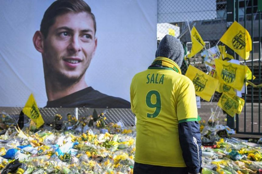 In this photo taken on Feb 10, supporters pay tribute and look at yellow flowers displayed in front of the portrait of Argentinian forward Emiliano Sala at the Beaujoire stadium in France.