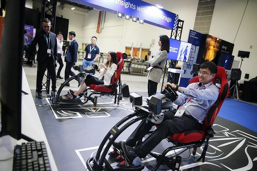 Visitors trying out a driving simulator at IBM Think Singapore yesterday. More than 1,000 business leaders and experts gathered for the one-day conference to discuss how companies around the world were using cutting-edge technology to transform their
