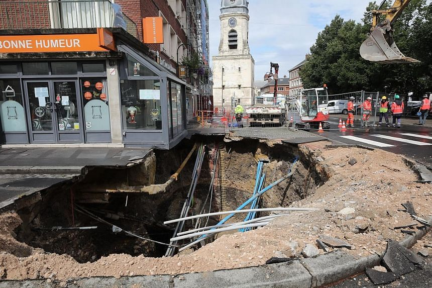 Construction workers at the site of a large sinkhole along a street in the city of Amiens, northern France, on Tuesday. The sinkhole - five metres deep and 10 metres wide - appeared in the centre of Amiens overnight on Sunday. The local municipal ser