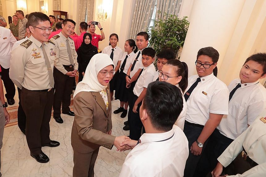 President Halimah Yacob mingling with APSN Tanglin School students who were a part of the National Day Parade Combined Drum Band, at a tea reception for NDP participants and organisers in the Istana yesterday.