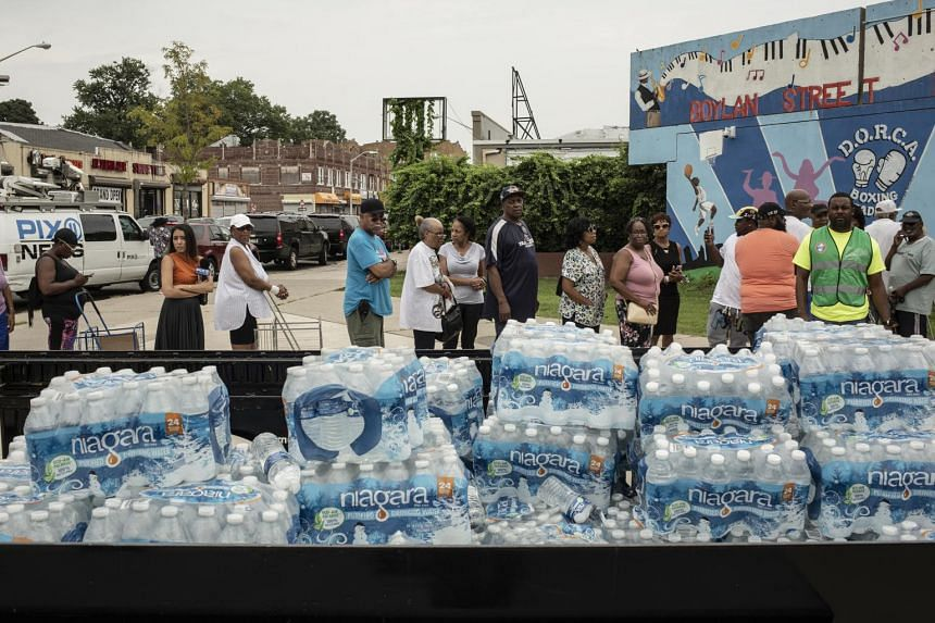 Hundreds of people waited in long lines in the summer heat to pick up cases of water.