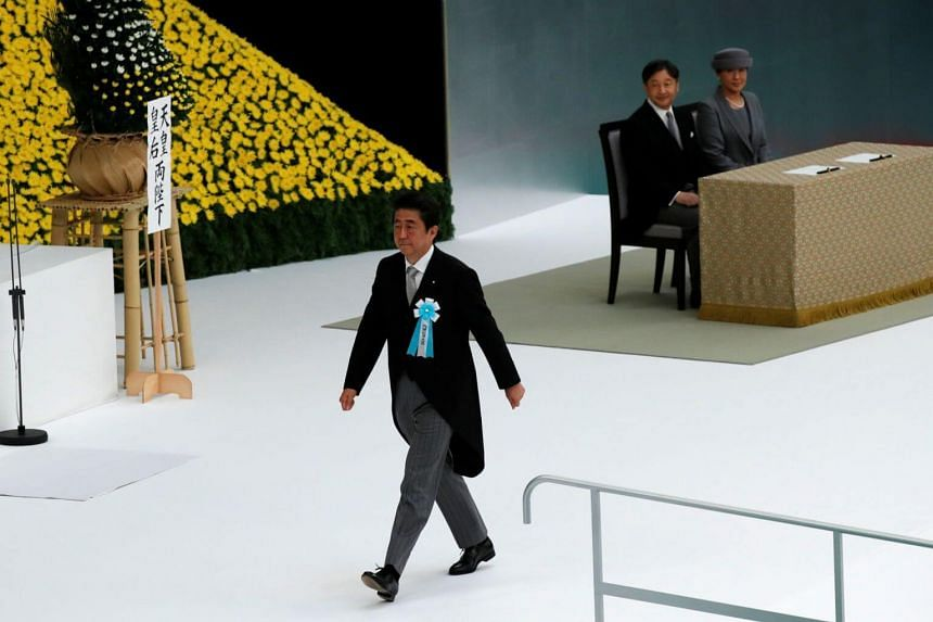 Japan's PM Shinzo Abe takes part in a memorial service ceremony marking the anniversary of Japan's surrender in World War II on Aug 15, 2019, while Emperor Naruhito and Empress Masako look on.