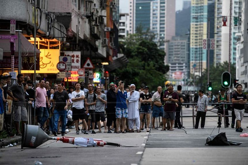 Residents gather after tear gas was fired at protesters in Sham Shui Po in Hong Kong, on Aug 11, 2019.