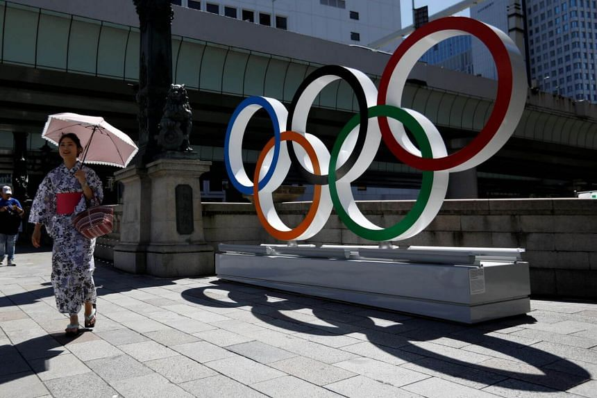 A woman wearing the yukata, or casual summer kimono, walks past Olympic rings displayed at Nihonbashi district in Tokyo, Japan, on Aug 5, 2019.