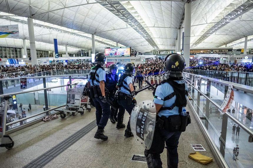 In a picture from Aug 13, 2019, police officers and protesters face off at Hong Kong International Airport.