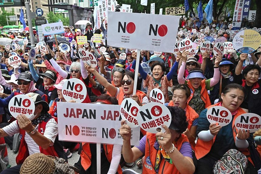 "South Korean protesters holding up signs reading ""No Abe's government"", referring to Japan's Prime Minister Shinzo Abe, during an anti-Japanese rally in central Seoul on Tuesday."