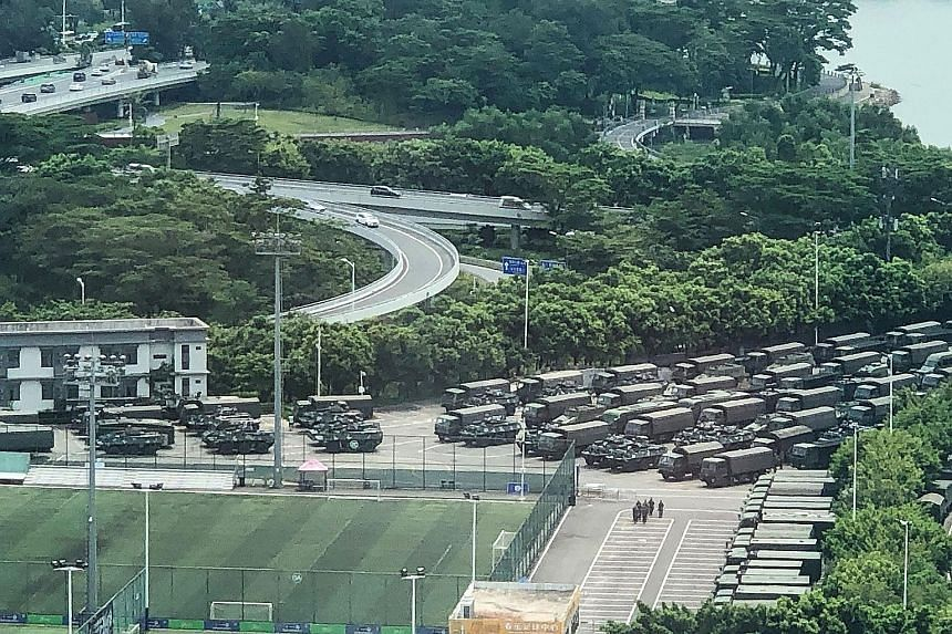 Chinese armed police (above) practising their tactics yesterday at the Shenzhen Bay Sports Centre in Shenzhen, just across the border from Hong Kong, while trucks and armoured personnel carriers (right) were seen parked outside.