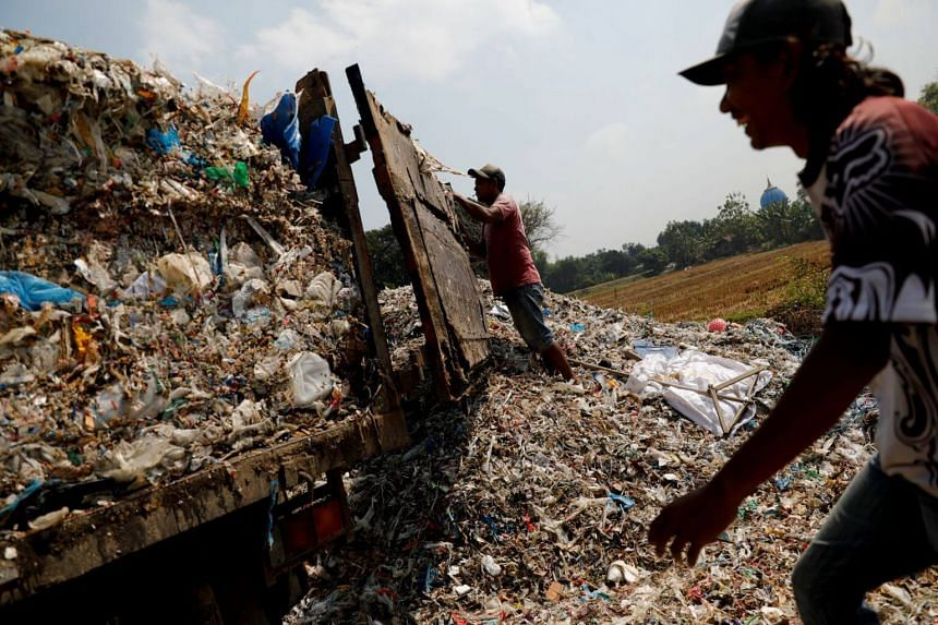 Workers prepare to unload waste next to paddy fields at Bangun village in Mojokerto, East Java province, Indonesia, on Aug 1, 2019. Sorting through piles of rubbish is a key source of income for the villagers.