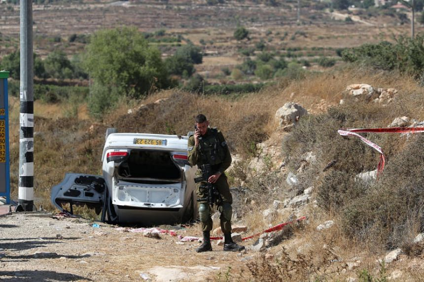 An Israeli soldier stands near the scene of what Israeli military said is a car-ramming attack near the settlement of Elazar in the Israeli-occupied West Bank, on Aug 16, 2019.