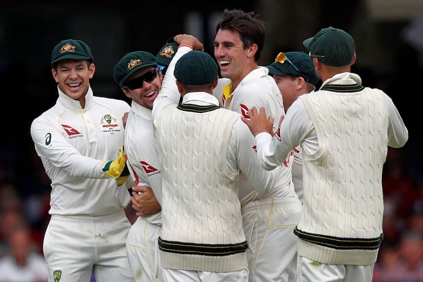 Australia's Pat Cummins (centre) celebrates with team mates after they took the wicket of England's Rory Burns for 53 runs.