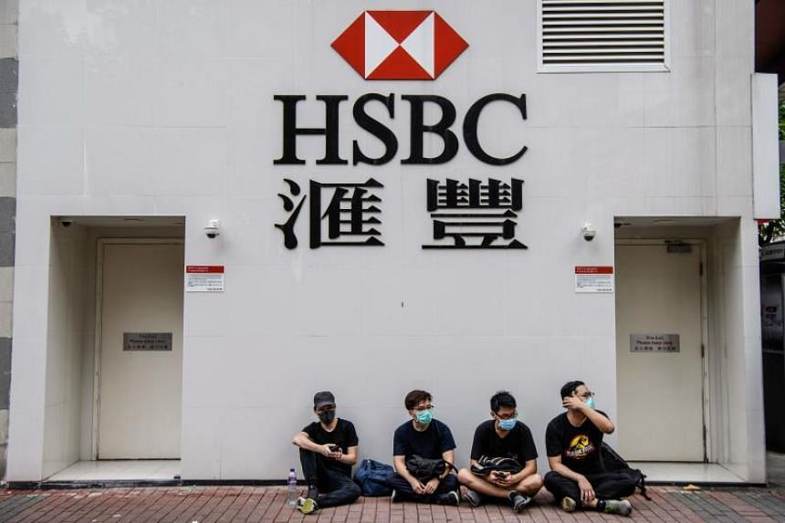 Protesters sit outside a HSBC branch in the Kowloon district of Hong Kong on Aug 11, 2019.