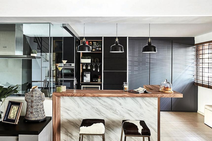 The marble and wood counter is where the family hangs out when the younger son demonstrates his culinary skills.