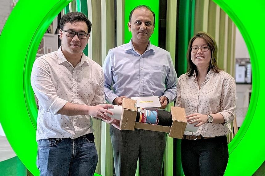 Mr Aditya Kumar, Schneider Electric's regional application centre leader, flanked by Nanyang Technological University students Chan Hao Yang and Charlene Lim, with a prototype of the system the two undergraduates came up with.