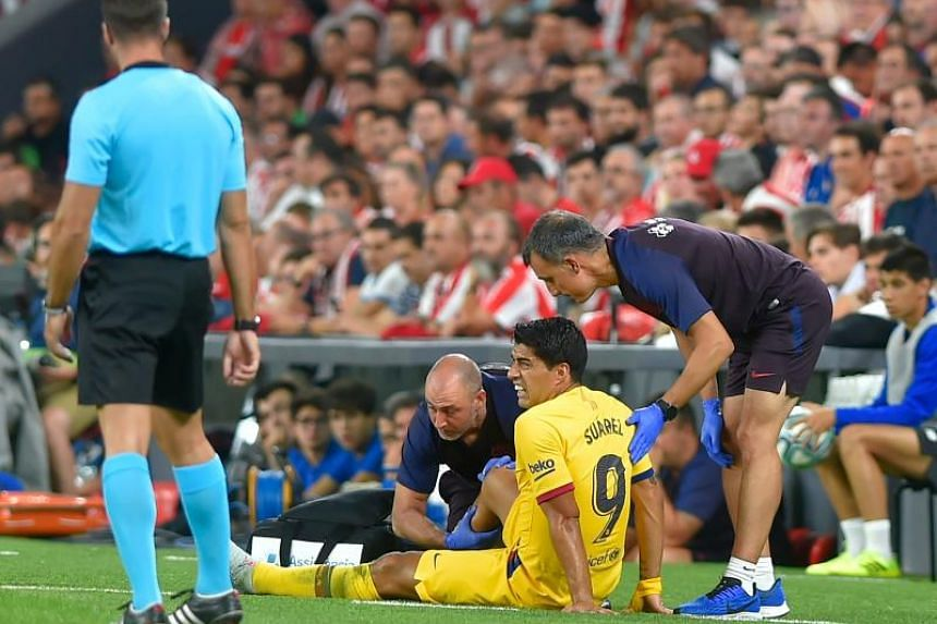 Doctors attend Barcelona's Uruguayan forward Luis Suarez during the Spanish league football match between Athletic Club Bilbao and FC Barcelona at the San Mames stadium in Bilbao on Aug 16, 2019.