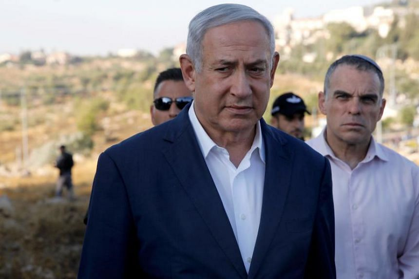 In a photo taken on Aug 8, Israel's Prime Minister Benjamin Netanyahu inspects the site where an off-duty Israeli soldier was found dead with stab wounds near the settlement of Migdal Oz in the occupied West Bank.