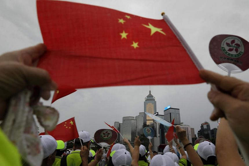 Pro-China supporters wave a Chinese national flag to support police and anti-violence during a rally in Hong Kong on Aug 17, 2019.
