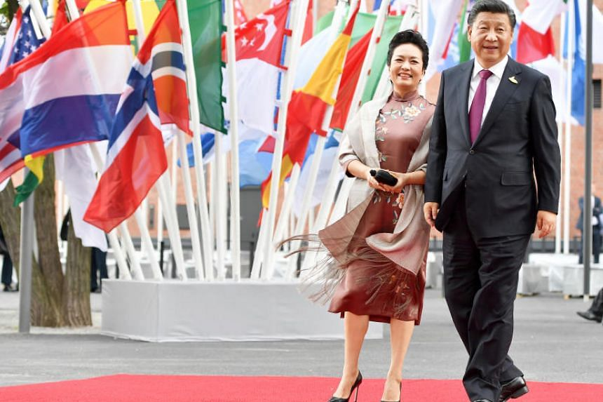 In a photo taken on July 7, 2017, Chinese President Xi Jinping and his wife Peng Liyuan pose on the red carpet as they attend to a concert at the 'Elbphilharmonie' as part of the G-20 summit in Hamburg, Germany.