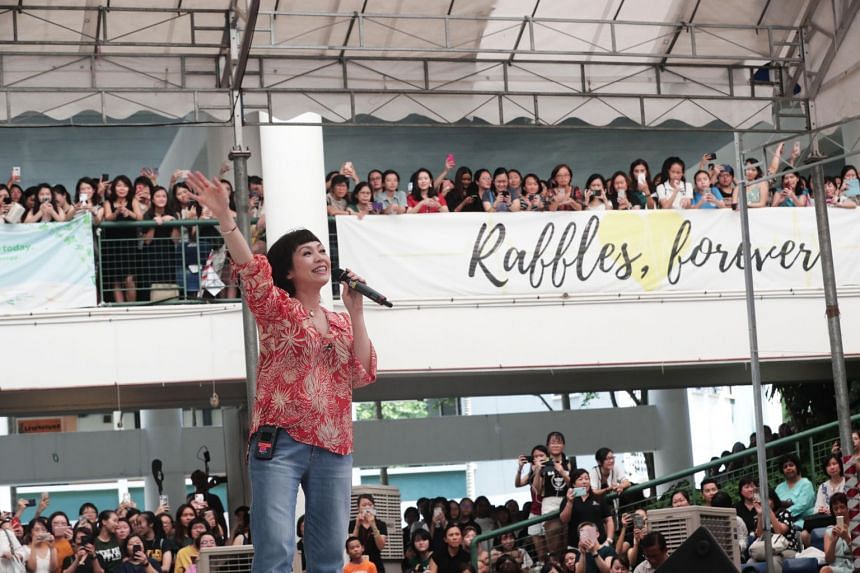 Raffles Girls' School alumna Kit Chan performs in the school's amphitheatre at its Anderson Road campus, leading event attendees in school cheers as well.