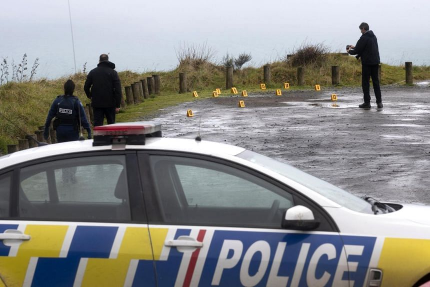 In a photo taken Aug 16, 2019, police collect and photograph evidence in the carpark of the Te Toto Gorge lookout on Whaanga Rd, south of Raglan, New Zealand.