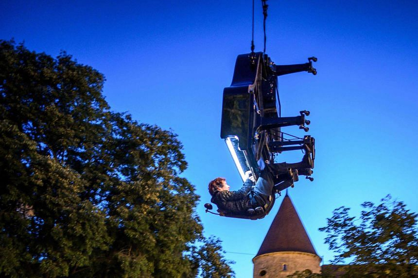 """Swiss pianist and composer Alain Roche hit the high notes at the crack of dawn yesterday, tickling the ivories while suspended with his grand piano by a moving crane for his performance Chantier, or """"construction site"""" in French. The show, inspired b"""