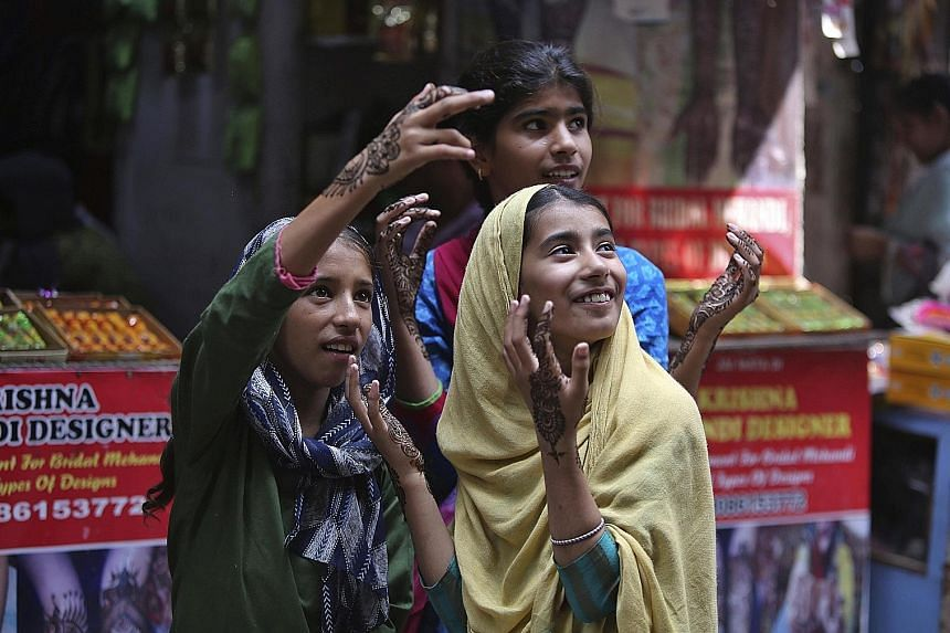 Girls with henna decorations to mark Eid al-Adha in Jammu last week. The Indian government said it eased restrictions for the festival. A New York Times image showing demonstrators outside Srinagar on Friday. Ongoing news reports of civilian victims