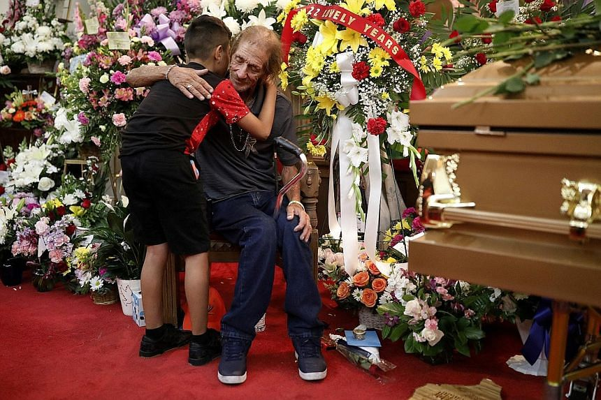Mr Antonio Basco, husband of Ms Margie Reckard, being embraced by a visitor as he sat next to her coffin on Friday. Ms Reckard was among 22 killed during the Aug 3 shooting. Mourners standing in line outside La Paz Faith Memorial and Spiritual Centre