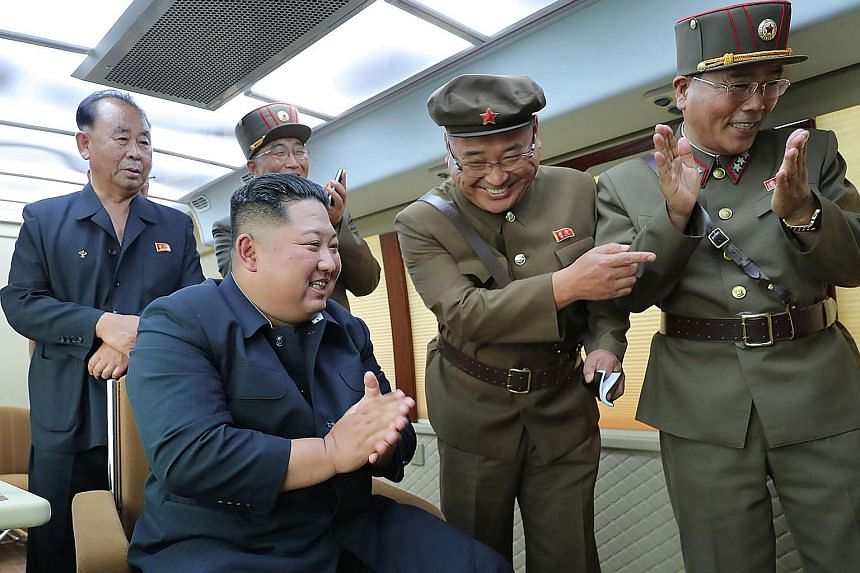 North Korean leader Kim Jong Un (seated) celebrating the successful test-firing of a new weapon at an undisclosed location on Friday.