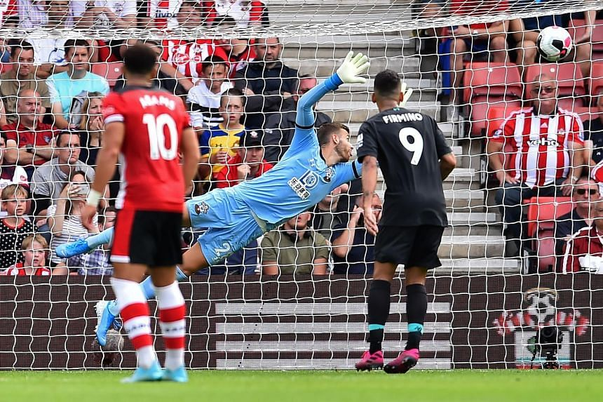 Southampton goalkeeper Angus Gunn diving in vain to stop Liverpool forward Sadio Mane's curling effort, which gave the Reds the lead at St Mary's Stadium. They went on to win 2-1. PHOTO: AGENCE FRANCE-PRESSE