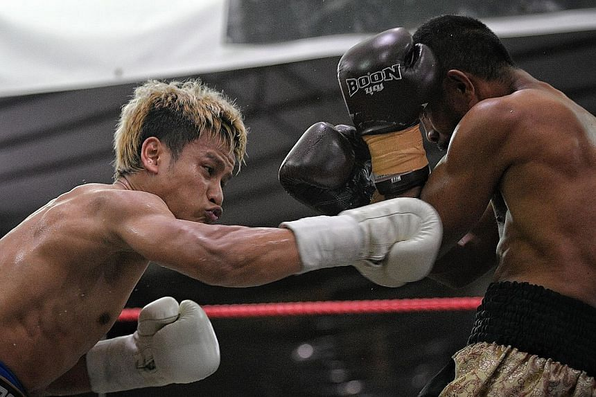 Singapore's professional boxer Muhamad Ridhwan (left) posted his second straight win after a technical knockout over Indonesian veteran Tommy Seran at the KBX 36 event at Joo Chiat Road yesterday. Ridhwan, 31, dominated the first two rounds of the si