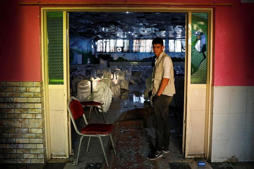 An Afghan man inspects a damaged wedding hall after a blast in Kabul, Afghanistan on Aug 18, 2019.
