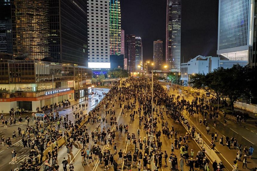 Thousands remain gathered outside the Central Government Complex, following the march from Victoria Park, with some turning their laser pointers on the government offices on Aug 18, 2019.