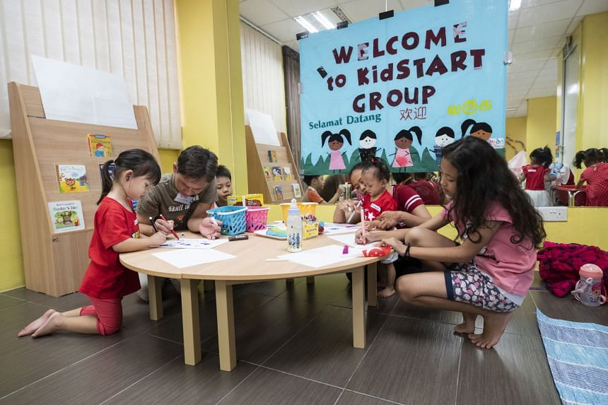 Parents and children interacting during a KidStart Group activity.