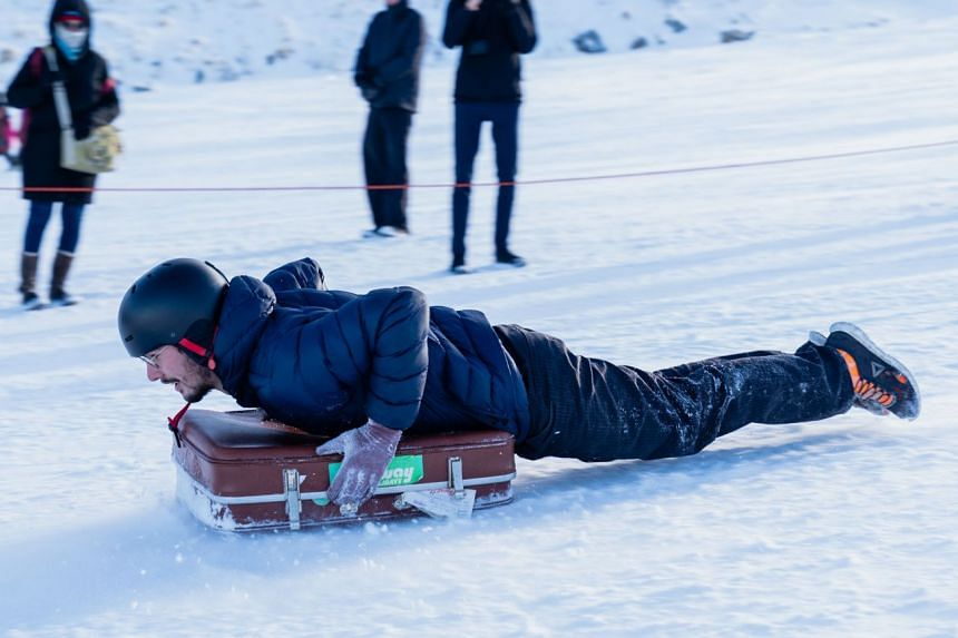 During the suitcase race at the Queenstown Winter Festival, competitors slide down the mountain on brown vintage luggage.