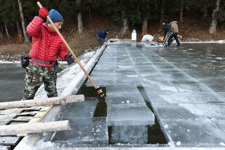 This picture taken on Jan 10, 2019 shows a worker removing a block of natural ice after it was cut from an open-air pool at a factory in Nikko, Tochigi prefecture.
