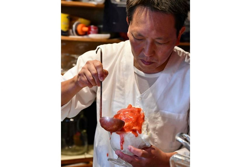 This picture taken on June 21, 2019 shows shop owner Koji Morinishi making a kakigori dessert with natural ice in the Yanaka district of Tokyo.