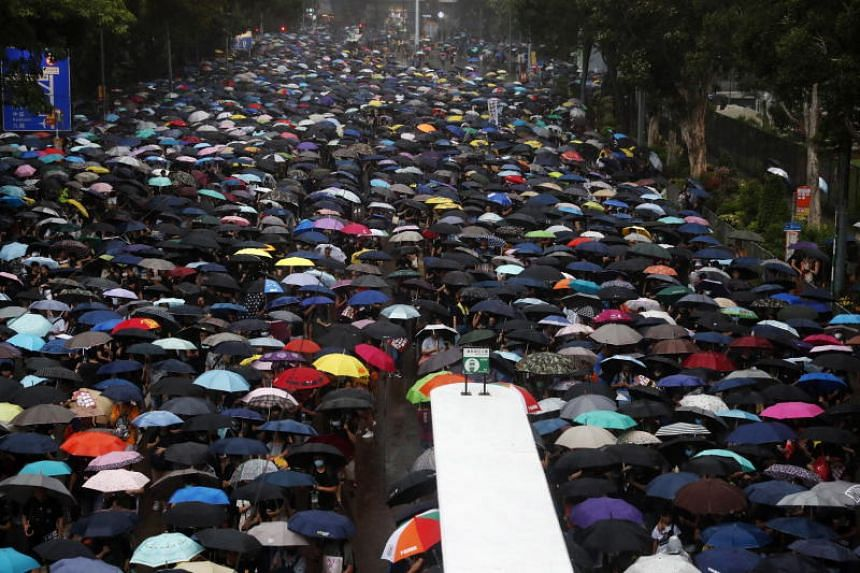 Protesters holding umbrellas amid heavy rain marching in an anti-government rally in Hong Kong on Aug 18, 2019.