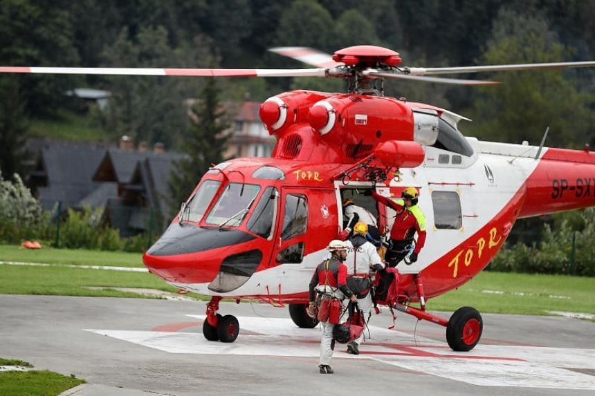 Members of a rescue team boarding a helicopter in Zakopane, Poland, on Aug 18, 2019, to join the search operation for two cave climbers trapped in the country's Tatra mountains.