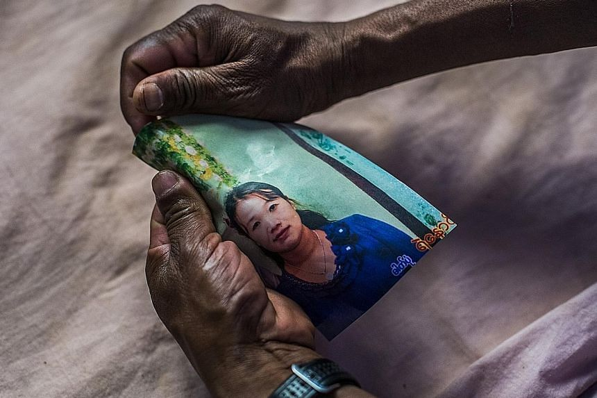 Nyo's father showing a picture of accused broker Daw Hnin Wai, who has fled and is wanted by the Myanmar police. PHOTOS: NYTIMES