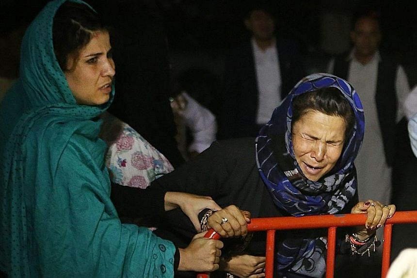 A grieving Afghan woman, who lost her husband and two sons, after a suicide attack on a wedding party in Kabul last Saturday. The strike underscores in part the inadequacy of Afghanistan's security forces. Workers inspecting the wedding hall yesterda