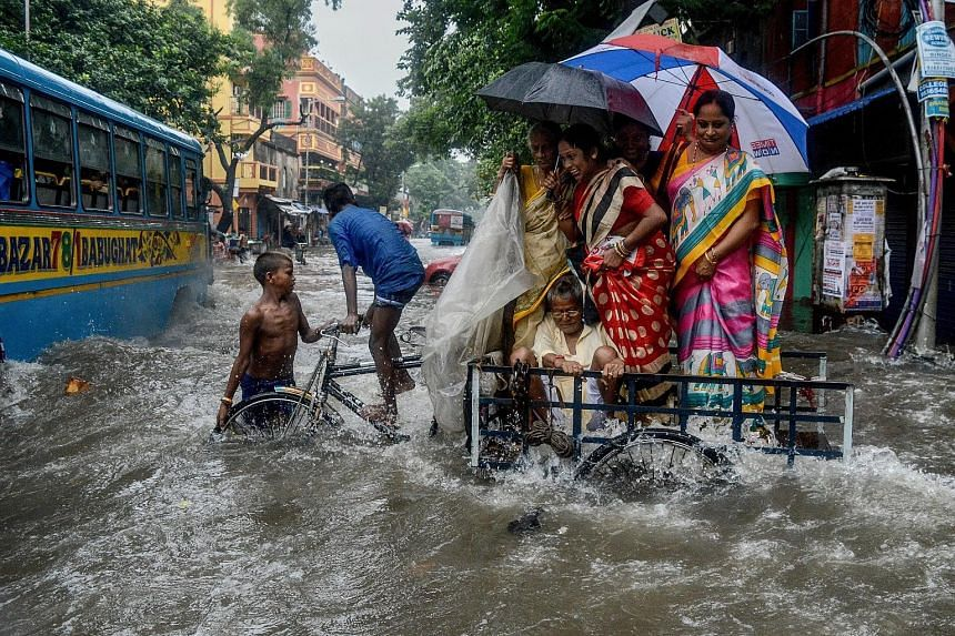 A family crossing a flooded road amid gushing water following heavy rain in Kolkata. Flood warnings were sounded in parts of northern India yesterday as the nationwide death toll in monsoon rains surpassed 1,000. India's monsoon season from June to S