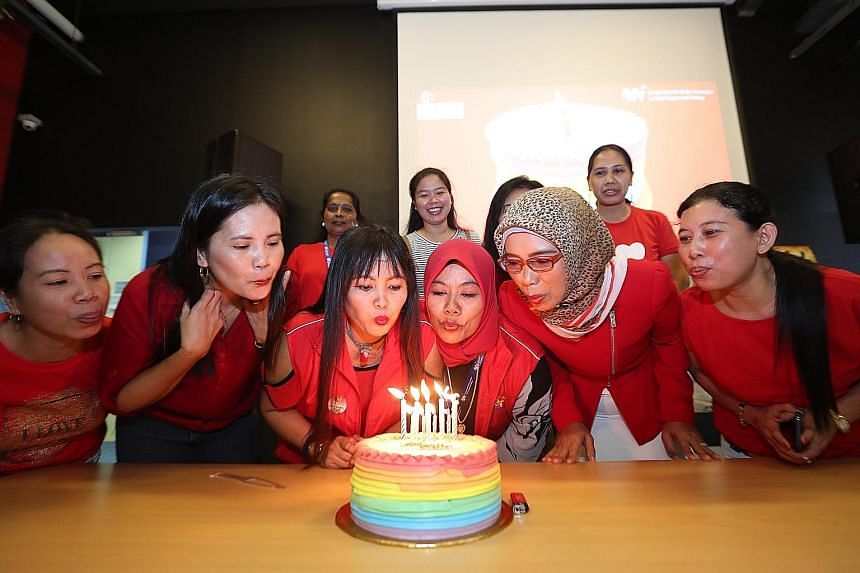 Indonesian Siti Mur Wati Bawel (third from left), who turns 41 today, joined other maids with August birthdays as well to blow out candles and cut a rainbow sponge cake yesterday.