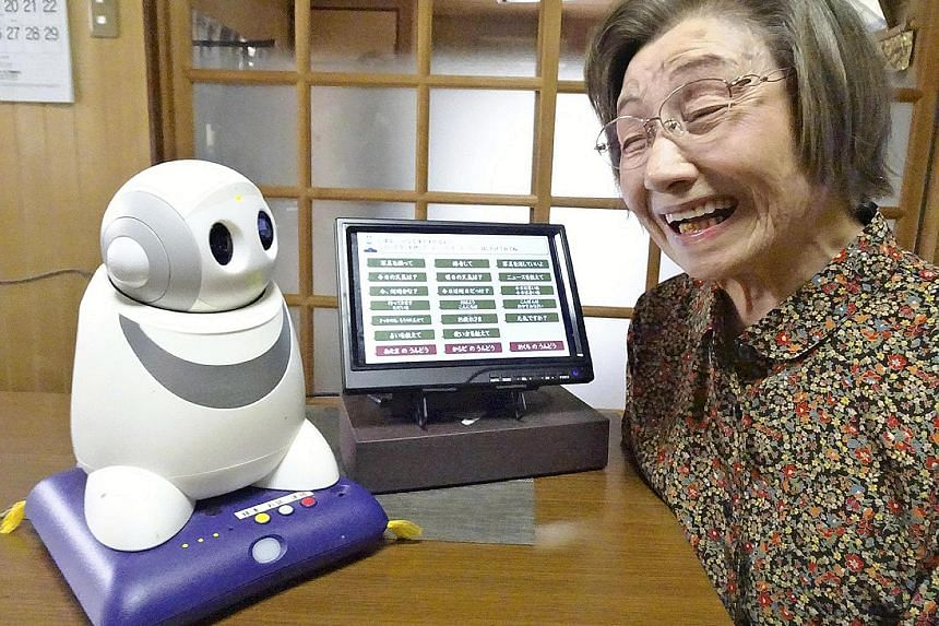 Ms Setsuko Saeki with her PaPeRo i robot, which greets her each morning when she gets up, asking if she slept well. It also makes impromptu puns and tells her pieces of trivia.