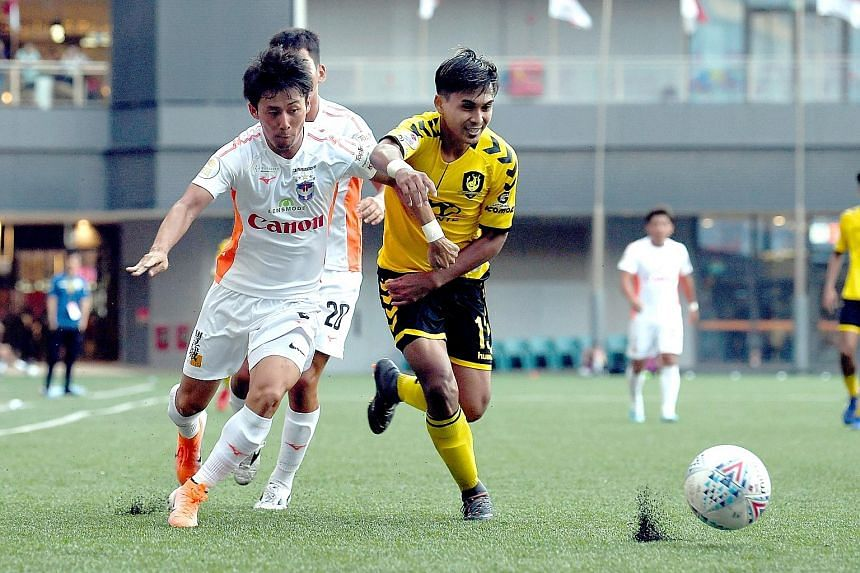 Tampines' Taufik Suparno and Hiroyoshi Kamata chasing the ball during their Singapore Premier League match at Our Tampines Hub yesterday. Tampines won 2-0 to consolidate third place, two points behind joint leaders Brunei DPMM and Hougang United. ST