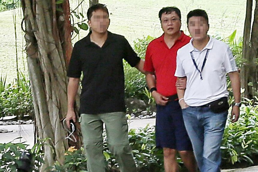 Laundry shop manager Leslie Khoo Kwee Hock (in red) admitted he strangled Ms Cui Yajie in his BMW and later burned her body in Lim Chu Kang Lane 8 over several days.