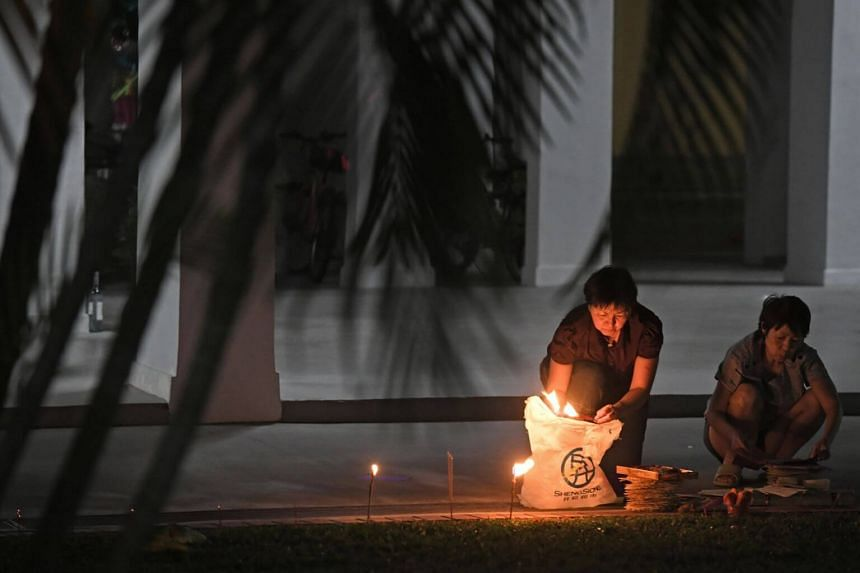 Residents burn offerings at a HDB block.