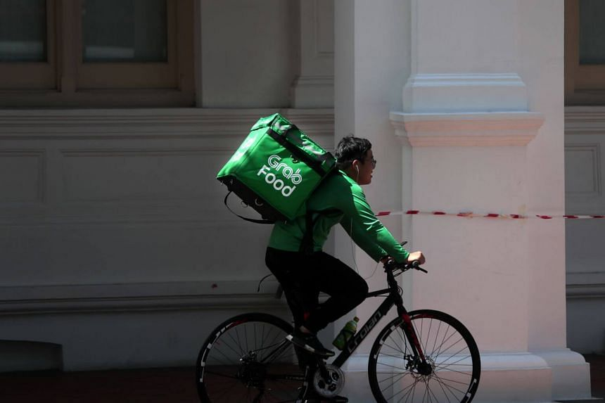 A GrabFood worker cycles along Raffles Hotel, on May 23, 2019.