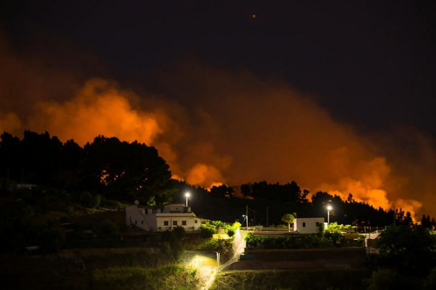 Flames and smoke from a forest fire are seen in the village of Valleseco, in the Canary Island of Gran Canaria, Spain, on Aug 18, 2019.