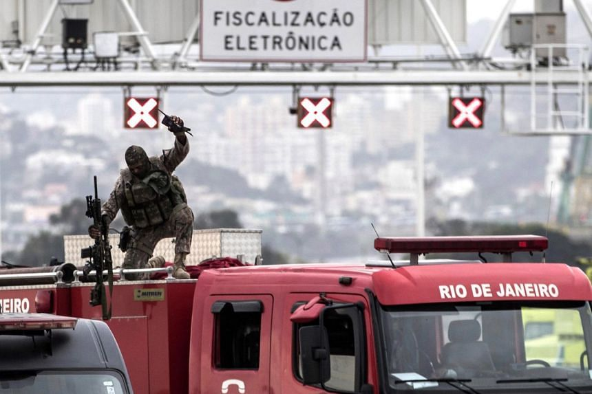 A police sniper celebrates after shooting a hijacker who was threatening bus passengers in Rio.