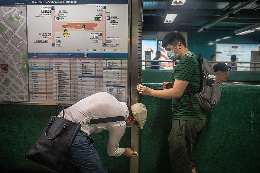 Activists cleaning an information board at Sham Shui Po MTR station in Hong Kong yesterday. Last week, police used tear gas to disperse protesters near the station. Weeks of protests have plunged Hong Kong into a crisis. PHOTO: EPA-EFE Protesters at