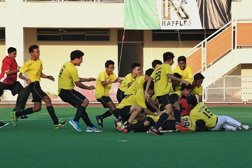 Victoria School's hockey players celebrate after winning a marathon penalty shoot-out against Raffles Institution to claim the Schools National C Division boys' hockey gold. ST PHOTO: KHALID BABA